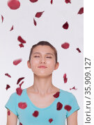 Beautiful tranquil young woman looking up with eyes closed with rose petals flying around her. Стоковое фото, агентство Ingram Publishing / Фотобанк Лори