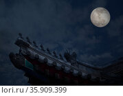 Close-up of ornate roof tiles on Chinese building with moon background, night. Стоковое фото, агентство Ingram Publishing / Фотобанк Лори