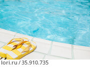 Pair of yellow flip flops by the pool side. Стоковое фото, агентство Ingram Publishing / Фотобанк Лори
