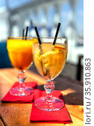 Two glass with lemonade or mojito cocktail with lemon, cold refreshing drink or beverage with ice on blur background. Стоковое фото, фотограф Евгений Ткачёв / Фотобанк Лори