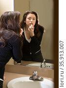 Woman putting on lipstick in restroom. Стоковое фото, фотограф Shannon Fagan / Ingram Publishing / Фотобанк Лори