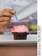 Person putting candle on cupcake. Стоковое фото, фотограф Shannon Fagan / Ingram Publishing / Фотобанк Лори