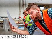 Arbeiter liest Zettel mit einer Bestellung in der Werkstatt einer... Стоковое фото, фотограф Zoonar.com/Robert Kneschke / age Fotostock / Фотобанк Лори