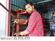 Arbeiter oder Handwerker in der Ausbildung im Materiallager einer... Стоковое фото, фотограф Zoonar.com/Robert Kneschke / age Fotostock / Фотобанк Лори