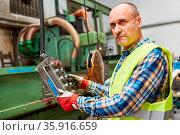 Arbeiter an Bedienfeld von Koordinatenbohrmaschine in Fabrik für ... Стоковое фото, фотограф Zoonar.com/Robert Kneschke / age Fotostock / Фотобанк Лори