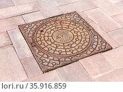 Samara, Russia - May 4, 2021: Metal cover manhole on the pavement road. Стоковое фото, фотограф Zoonar.com/Alexander Blinov / easy Fotostock / Фотобанк Лори