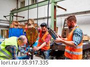 Arbeiter Team in der Fabrikhalle befestigt Last an Kranhaken in der... Стоковое фото, фотограф Zoonar.com/Robert Kneschke / age Fotostock / Фотобанк Лори