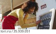 African american woman wearing apron writing on food menu slate board of the food truck. Стоковое видео, агентство Wavebreak Media / Фотобанк Лори