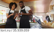 African american couple wearing aprons smiling while using digital tablet in the food truck. Стоковое видео, агентство Wavebreak Media / Фотобанк Лори