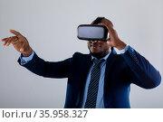 African american businessman wearing vr headset gesturing against grey background. Стоковое фото, агентство Wavebreak Media / Фотобанк Лори