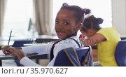 Portrait of happy african american schoolgirl sitting at classroom, making notes, looking at camera. Стоковое видео, агентство Wavebreak Media / Фотобанк Лори