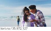Happy group of diverse female friends having fun, walking along beach using smartphone. Стоковое видео, агентство Wavebreak Media / Фотобанк Лори