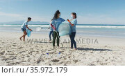 Diverse group of women wearing volunteer t shirts and face masks picking up rubbish from beach. Стоковое видео, агентство Wavebreak Media / Фотобанк Лори