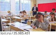 Friendly male teacher working with teen students in classroom at school. Стоковое видео, видеограф Яков Филимонов / Фотобанк Лори