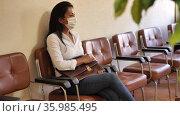 Focused adult hispanic woman in protective face mask sitting on chair in office corridor, waiting for job interview. Pandemic precautionary concept. Стоковое видео, видеограф Яков Филимонов / Фотобанк Лори