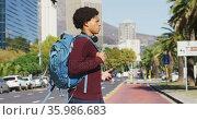 African american man in city, using smartphone, wearing headphones and backpack crossing street. Стоковое видео, агентство Wavebreak Media / Фотобанк Лори