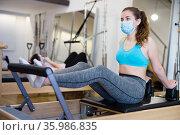Woman protective mask doing pilates exercises lying on pilates machines. Стоковое фото, фотограф Яков Филимонов / Фотобанк Лори