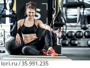 Charming woman with curly hair sits on the floor in the gym on the... Стоковое фото, фотограф Zoonar.com/Andrey Bezuglov / easy Fotostock / Фотобанк Лори