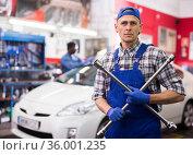 Qualified mechanic changes tires on car in car service. Стоковое фото, фотограф Яков Филимонов / Фотобанк Лори