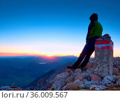 Tired hiker sit on border stone on Alpine mountain. Austria Germany... Стоковое фото, фотограф Zoonar.com/rdonar / easy Fotostock / Фотобанк Лори