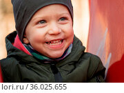 Happy little boy with a cap laughing loudly sitting on a children... Стоковое фото, фотограф Zoonar.com/Roberto Binetti Photographer / age Fotostock / Фотобанк Лори