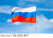 Russian state flag waving in the wind against the blue sky. Стоковое фото, фотограф Zoonar.com/Alexander Blinov / easy Fotostock / Фотобанк Лори