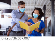 Diverse male and female colleague in face masks discussing paperwork in office corridor. Стоковое фото, агентство Wavebreak Media / Фотобанк Лори