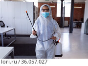 Portrait of cleaner wearing ppe suit, glasses and mask disinfecting office workspace. Стоковое фото, агентство Wavebreak Media / Фотобанк Лори