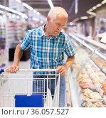 mature senor choosing prepared food in cooking department of supermarket. Стоковое фото, фотограф Татьяна Яцевич / Фотобанк Лори