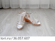 White women's leather sandals made of genuine leather with cork podosh stand on floor in the room. Стоковое фото, фотограф Володина Ольга / Фотобанк Лори