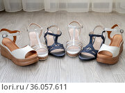 White and blue women's leather sandals stand on the floor in the room. Стоковое фото, фотограф Володина Ольга / Фотобанк Лори