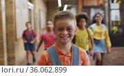 Portrait of happy caucasian schoolboy standing in corridor looking at camera. Стоковое видео, агентство Wavebreak Media / Фотобанк Лори