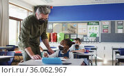 Diverse male teacher helping schoolgirl sitting in classroom, all wearing face masks. Стоковое видео, агентство Wavebreak Media / Фотобанк Лори