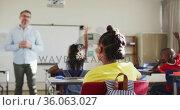 Happy caucasian male teacher in classroom with children raising hands during lesson. Стоковое видео, агентство Wavebreak Media / Фотобанк Лори