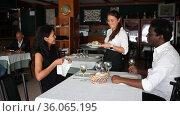 smiling female waiter bringing order to group of friens in restaurante. Стоковое видео, видеограф Яков Филимонов / Фотобанк Лори