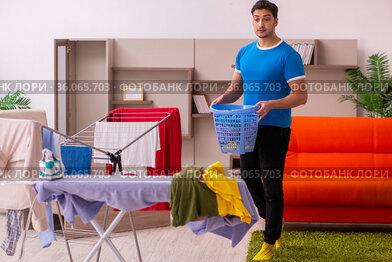 Young man husband doing ironing at home