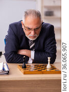 Old male employee playing chess at workplace. Стоковое фото, фотограф Elnur / Фотобанк Лори