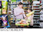 mother with daughter choosing refreshing beverages in supermarket. Стоковое фото, фотограф Яков Филимонов / Фотобанк Лори