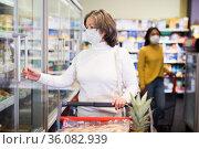 Mature woman in protective mask choosing food products on shelves in shop. Стоковое фото, фотограф Яков Филимонов / Фотобанк Лори