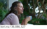 Thoughtful senior caucasian woman standing on terrace drinking coffee and looking around. Стоковое видео, агентство Wavebreak Media / Фотобанк Лори