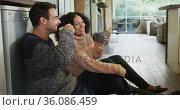 Happy diverse couple talking and drinking coffee sitting on floor in kitchen. Стоковое видео, агентство Wavebreak Media / Фотобанк Лори