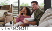 Smiling mixed race couple eating popcorn while watching a movie together at vacation home. Стоковое видео, агентство Wavebreak Media / Фотобанк Лори