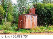 Old voltage power transformer substation at the village in summertime. Стоковое фото, фотограф Zoonar.com/Alexander Blinov / easy Fotostock / Фотобанк Лори