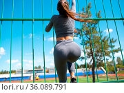 Girl climb the fence of stadium. Young sport woman going to run training... Стоковое фото, фотограф Zoonar.com/Max / easy Fotostock / Фотобанк Лори
