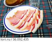 Slices of fresh sliced bacon on a plate. Стоковое фото, фотограф Яков Филимонов / Фотобанк Лори