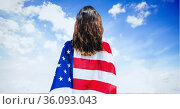 Composition of woman wrapped in american flag against clouds on blue sky. Стоковое фото, агентство Wavebreak Media / Фотобанк Лори
