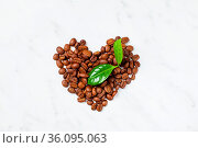 Heart shape from above handful pile of the roasted coffee beans with... Стоковое фото, фотограф Zoonar.com/Oksana Shufrych / easy Fotostock / Фотобанк Лори