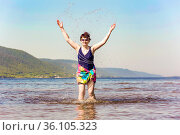 lovely sporty mature woman stands and splashes water on the beach on the Volga river on a summer sunny day against the background of mountains. Стоковое фото, фотограф Акиньшин Владимир / Фотобанк Лори