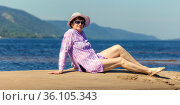 beautiful mature woman lies on a small sandy island in the middle of the Volga river. Стоковое фото, фотограф Акиньшин Владимир / Фотобанк Лори