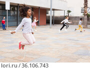 Tween African American girl skipping rope in schoolyard. Стоковое фото, фотограф Яков Филимонов / Фотобанк Лори